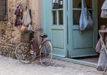 Vintage Fahrrad an der Tür eines Hauses in einer mittelalterlichen Stadt an der Costa Brava