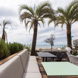 Terrasse mit Tischen und Sitzplätzen direkt am Meer im Hotel Marítim